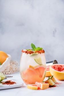 Mezcal- oder mescal-paloma-cocktail mit grapefruit, selterswasser und limettensalzrand im glas