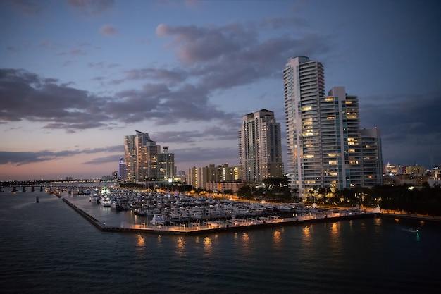 Miami, south beach moderne gebäude in der nähe von wasser in der bucht mit vielen booten bei sonnenuntergang und leuchtenden lichtern auf bewölktem abendhimmelhintergrund, nachtszene