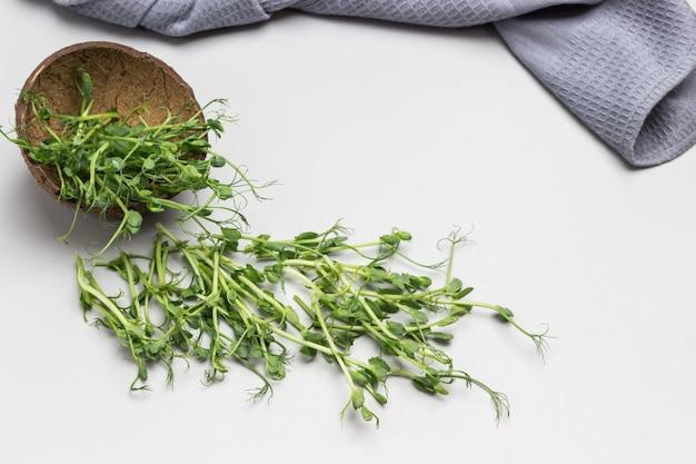 Microgreen erbsensprossen auf dem tisch. graue serviette. draufsicht. grauer hintergrund