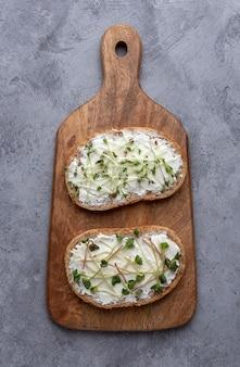 Microgreens auf sandwiches mit getreidebrot auf einem schneidebrett auf einer grauen oberfläche