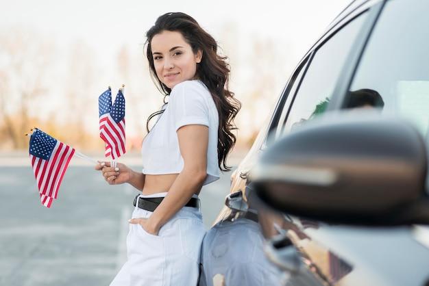Mid shot brünette frau hält usa flaggen in der nähe von auto