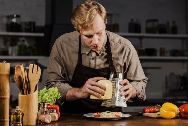 Mid shot chef, der käse reibt