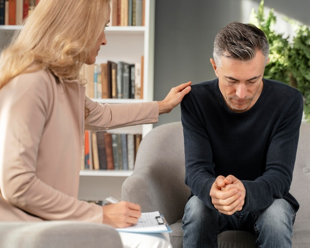 Mid shot frau therapeut tröstet mann