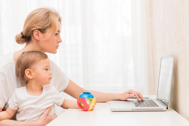Mid shot mutter hält baby am schreibtisch arbeiten