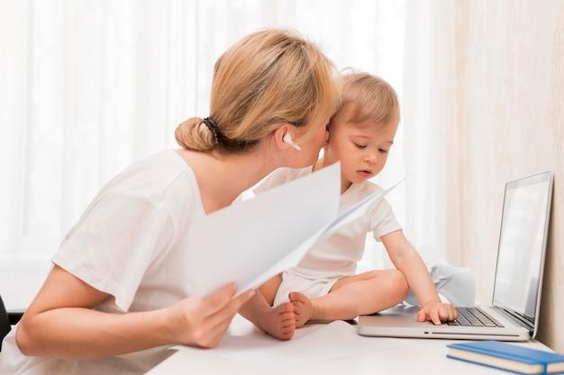 Mid shot mutter hält papiere und küsst baby auf schreibtisch
