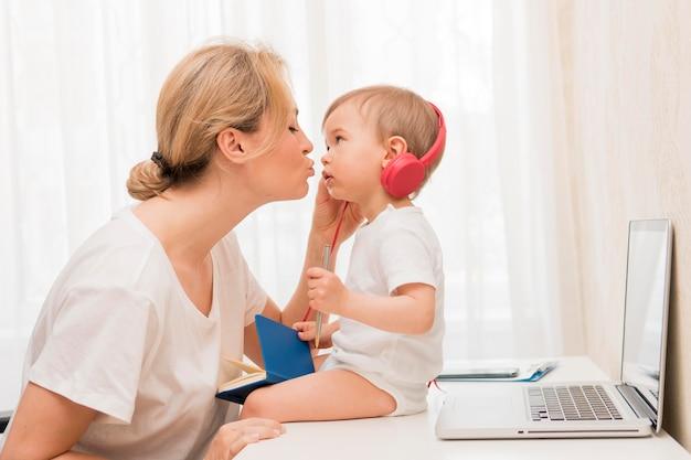 Mid shot mutter küsst baby auf schreibtisch mit kopfhörern
