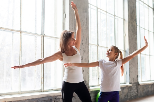 Mid shot mutter und tochter strecken sich im fitnessstudio