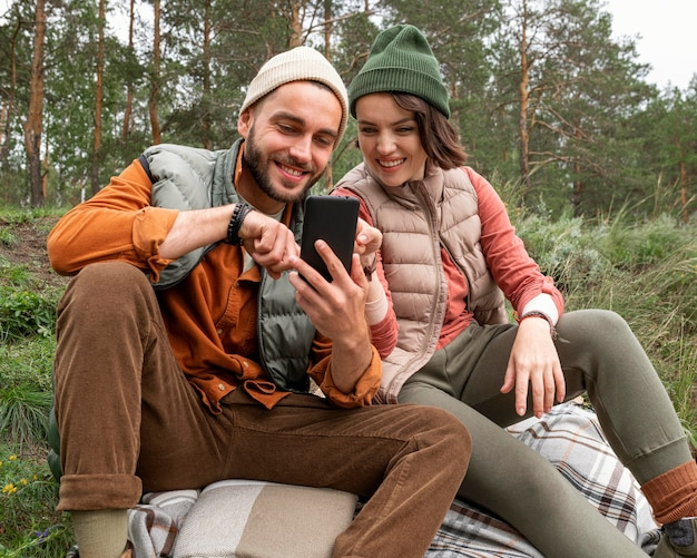 Mid shot paar sitzt auf gras und schaut auf telefon
