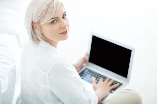 Midadult frau, die auf laptop drinnen tippt. weibliches surfen