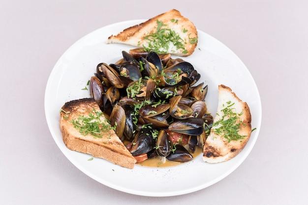 Miesmuscheln in sauce mit petersilie, french toast und zitrone. meeresfrüchte. muscheln in den muscheln.