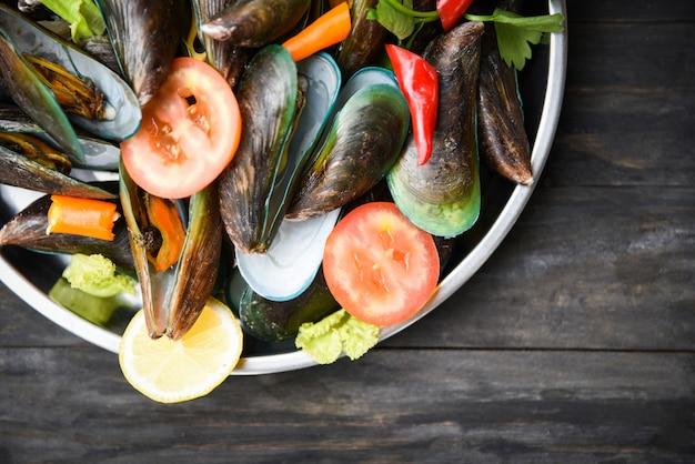 Miesmuscheln mit kräutern und gewürzen auf tablett kochten dampfende meeresfrüchte der grünen miesmuschel