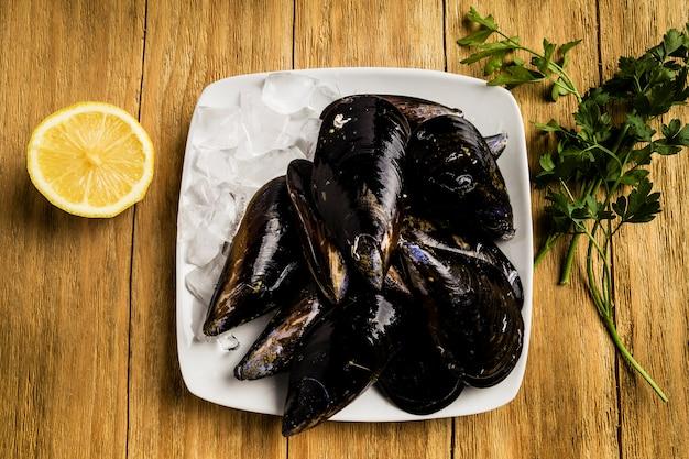 Miesmuscheln, petersilie und eine halbe zitrone auf weißen platten mit eis