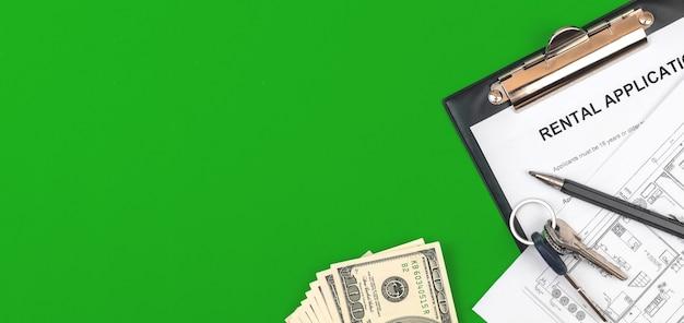 Mietformular in der zwischenablage. bürodesktop mit vertrag, geld, hausschlüsseln und stift. grüner hintergrund, foto von oben