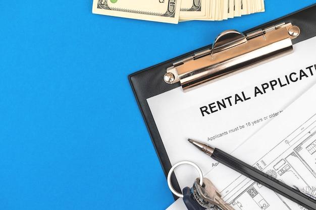 Mietvertrag auf zwischenablage. bürodesktop mit vertrag, geld, hausschlüsseln und stift. blauer hintergrund, foto von oben