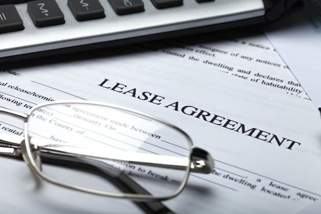 Mietvertragsdokumente mit brille, stift und taschenrechner