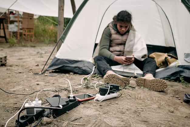 Migrantenmädchen aus dem nahen osten, das im zelt an steckdosen sitzt und das smartphone benutzt, während es im flüchtlingslager aufgeladen wird