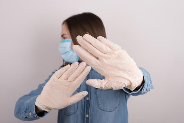 Mikrobenkonzept vermeiden. foto des verängstigten verängstigten, ängstlichen, ängstlichen teenager-mädchens, das ein problem hat, möchte von der quarantäne weglaufen und die isolierte graue wand testen Premium Fotos