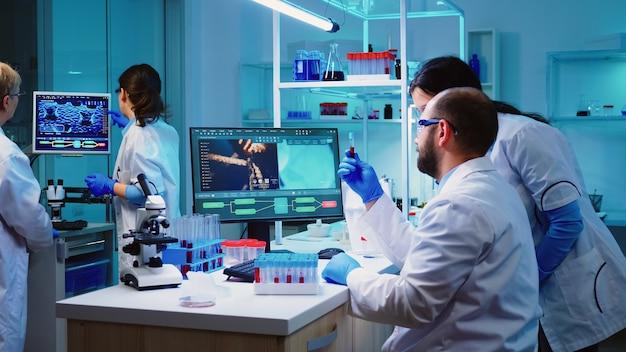 Mikrobiologe arzt, der ein blutprobenröhrchen aus einem gestell mit analysegeräten im laborhintergrund nimmt