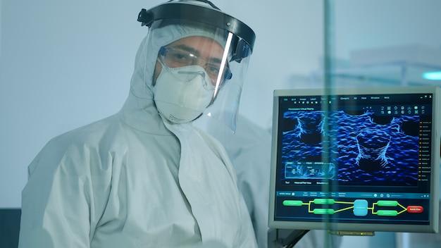 Mikrobiologe im ppe-anzug, der im labor steht und die kamera hinter der glaswand im ausgestatteten labor betrachtet. arzt untersucht die virusentwicklung mit hightech- und chemiewerkzeugen für die impfstoffentwicklung
