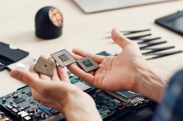 Mikrochips in männlichen händen in der werkstatt