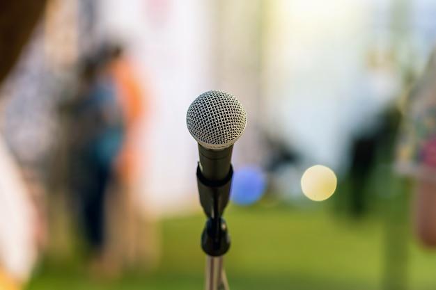 Mikrofon auf dem stadium über dem abstrakten unscharfen foto des grünen grases