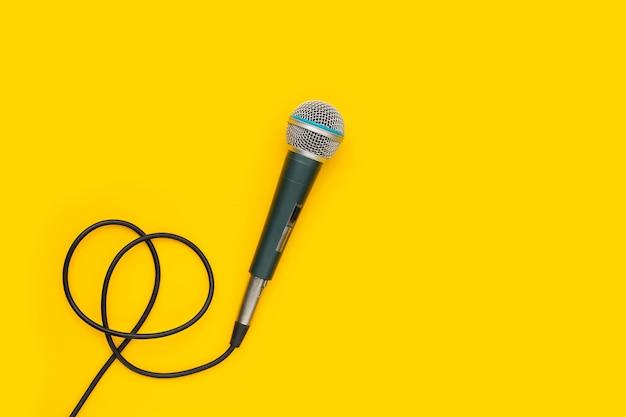 Mikrofon auf gelbem hintergrund. ansicht von oben