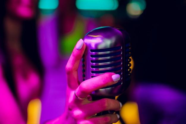 Mikrofon auf stand-up-comedy-bühne mit reflektorstrahl, kontrastreiches bild