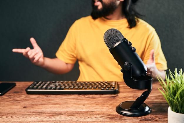 Mikrofon bei der ausstrahlung eines hausgemachten studios mit einem jungen mann, der live plaudert
