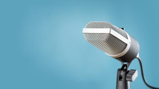 Mikrofon für audioaufzeichnung oder podcast-konzept, einzelnes mikrofon auf weichem blauem hintergrund mit kopienraum