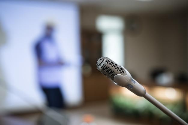 Mikrofon für rede auf abstraktem unscharfem konferenzsaal