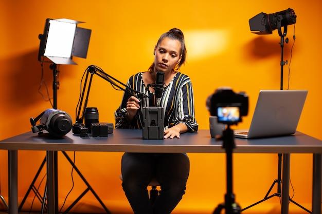 Mikrofon halten und über batterie für professionelle videokamera sprechen