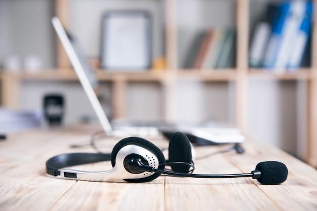 Mikrofon-headset mit notebook-computer auf arbeitstisch