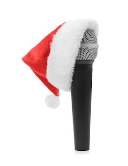Mikrofon in der weihnachtsmütze auf weiß. weihnachtsmusikkonzept