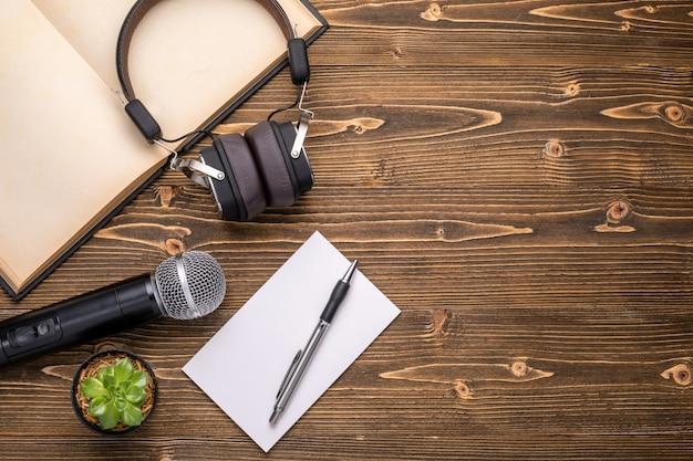 Mikrofon, kopfhörer, buch und papiernotiz auf braunem holzbrett. das sprechen lernen