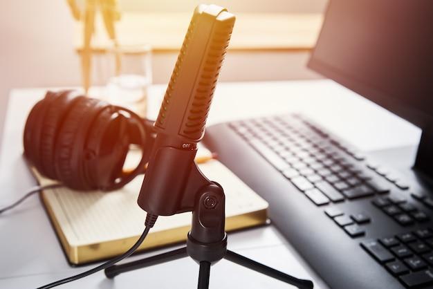 Mikrofon, kopfhörer und computermonitor auf dem tisch. online-podcast-konzept