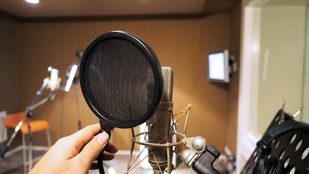Mikrofon mit shockmount und pop-filter auf stativ und notenständer bei der aufnahme von tonstudio-videos