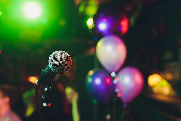 Mikrofon mit unscharfem buntem hellem licht in dunklem nachthintergrund, weichzeichnerbild für kommunikationskonzepte der geschäftstechnologie.