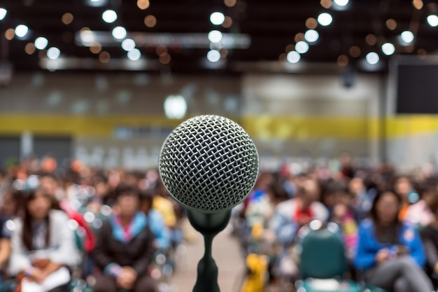 Mikrofon über dem abstrakten unscharfen foto des konferenzsaals oder des seminarraums in der ausstellungsmitte b