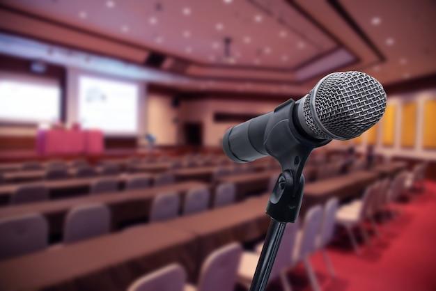 Mikrofon über dem unscharfen forum sitzungs-konferenz-training, das trainerraum konzept, unscharfen hintergrund lernt.