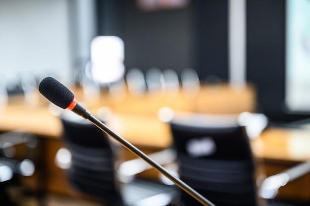 Mikrofon über dem unscharfen geschäftsforum sitzungs- oder konferenz-training, das anleitung room concept lernt