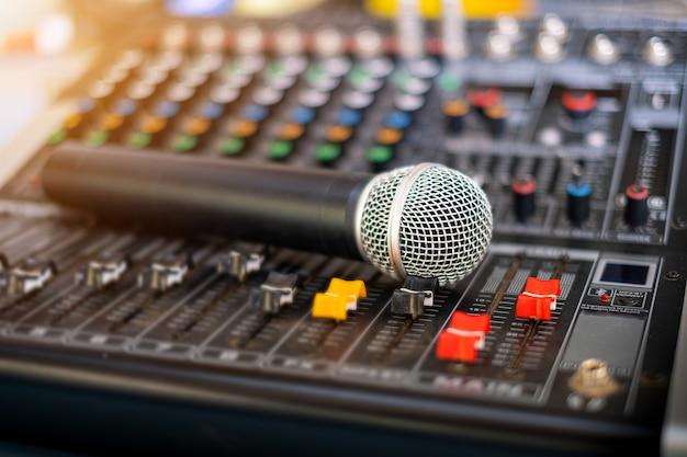 Mikrofon und audio-tonmischer analog im tonregieraum auf unscharfem hintergrund