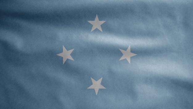 Mikronesische flagge weht im wind. mikronesien-banner bläst glatte seide. stoff stoff textur fähnrich hintergrund.