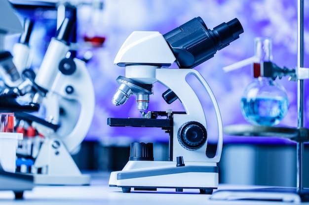 Mikroskop in und labor mit chemischer reagenzglasausrüstung im laborblaulicht, wissenschafts- und experimentkonzept.