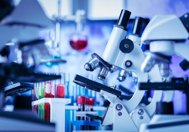 Mikroskop in und labor- und reagenzglasausrüstung im laborblaulicht, wissenschafts- und experimentkonzept.