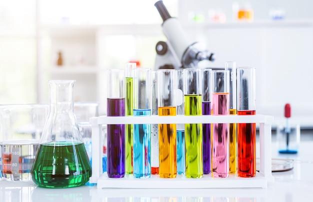 Mikroskop und reagenzgläser mit laborglas im laborhintergrund, forschung und wissenschaftliches konzept