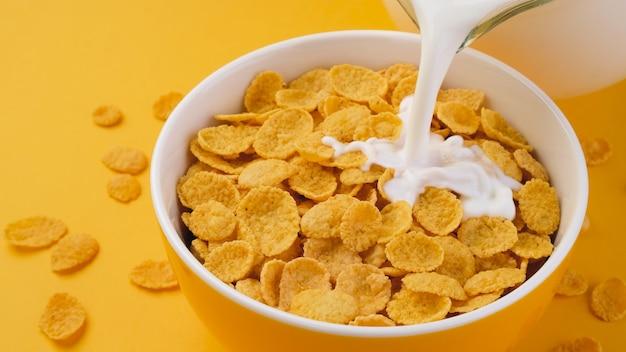 Milch gießt in schüssel cornflakes, draufsicht