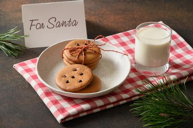 Milch im glas und hausgemachte kekse warten auf den weihnachtsmann.