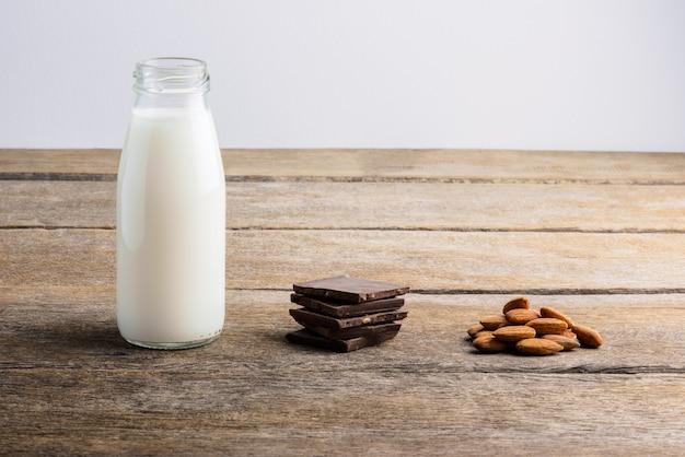 Milch in der flasche, in der schokolade und in der mandel auf hölzernem