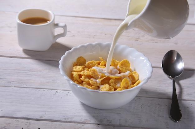Milch in eine schüssel cornflakes-müsli gießen und mit espressokaffee abdecken.