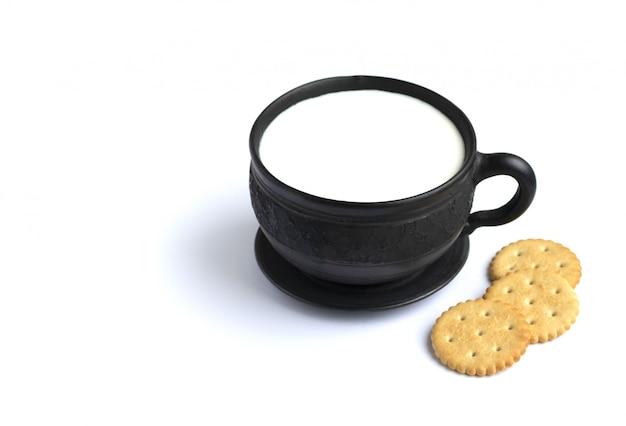 Milch in einem schwarzen becher und kekse